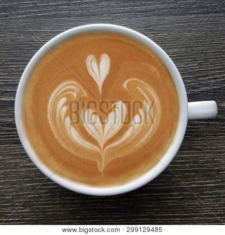 Top View Of A Mug Of Latte Art Coffee On Timber Background.