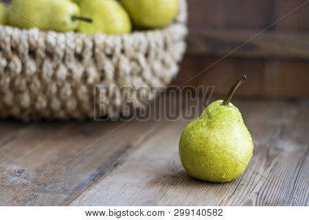 One Fresh Ripe Organic Yellow Pear On Rustic Wooden Brown Table With Defocused Pears In Basket On Ba