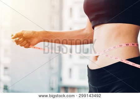 Beautiful Woman Using Tape Measuring Waist, Her Is Body Slim After Workout At Fitness Gym