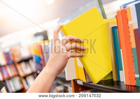 Bestseller Publishing Concept. Male Hand Choosing And Picking Yellow Book From Wooden Bookshelf In B
