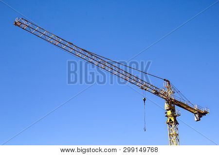 Yellow Crane Hoist. Yellow Crane Hoist With Blue Sky In The Background. Hoisting Crane Against A Bac