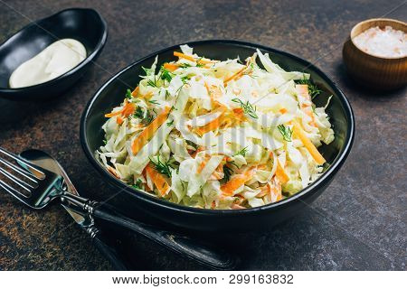 Traditional Cole Slaw Salad In A Black Bowl. Fresh Cabbage And Carrot Salad With Mayonnaise. Dark Ba