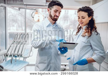 Healthcare And Medicine Concept,two Colleagues Looking At Screen Of The Tablet.