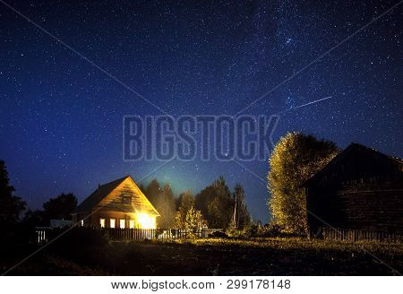 Majestic Milky Way And The Shooting Star Above The Village House In Summer. A Starry Night Sky. Wood