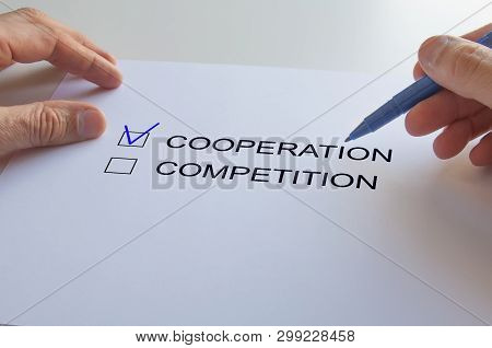 Questionnaire,cooperation And Competition, Word Cooperation With A Blue Check Mark, Pen In Hand.