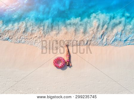Aerial View Of The Beautiful Young Lying Woman With Pink Donut Swim Ring On The White Sandy Beach Ne