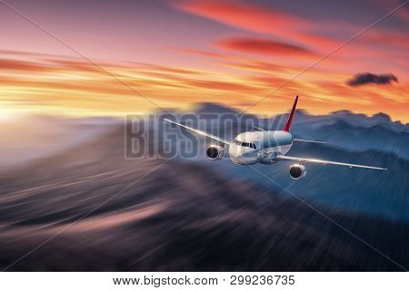 Airplane In Motion. Aircraft With Motion Blur Effect Is Flying Over Hills And Mountains At Sunset. P