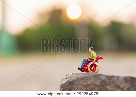 Miniature People : Disabled Man Sitting In Wheelchair  On The Rock Cliff And Copy Space For Text
