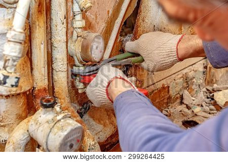 Dismantling Of Old Plumbing. Close Up Of Plumbing Hands With Adjustable Wrench