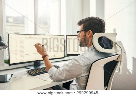 Analyzing Data. Back View Of Young Businessman Or Trader Pointing On The Data On Computer Screen Wit
