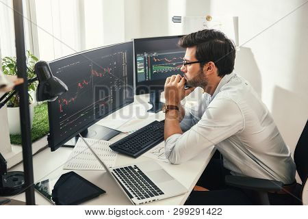 Successful Trader. Back View Of Bearded Stock Market Broker In Eyeglasses Analyzing Data And Graphs