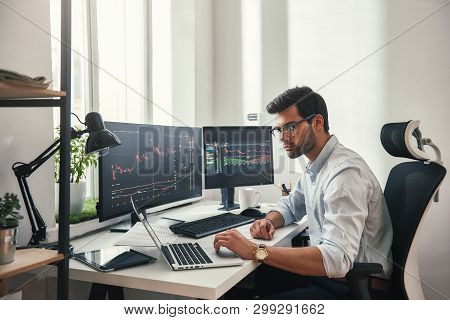 Busy working day. Young bearded trader in eyeglasses working with laptop while sitting in his modern office in front of computer screens with trading charts. poster