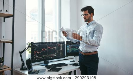 Analyzing Data. Thoughtful Trader In Eyeglasses Holding A Financial Report And Analyzing Trading Cha