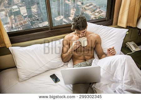 Naked Young Man In Bed With Coffee Or Tea Cup