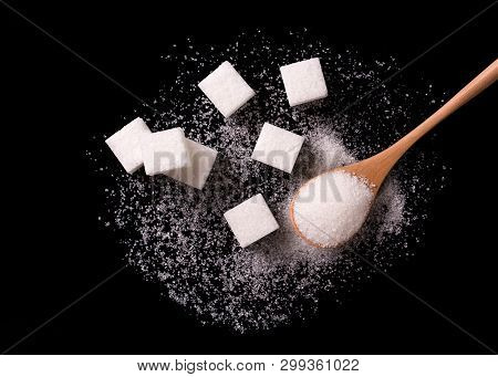 Sugar Scattered From Wooden Spoons On A Black Background. Sugar Wave. Sugar Sand And Sugar Cubes Pou