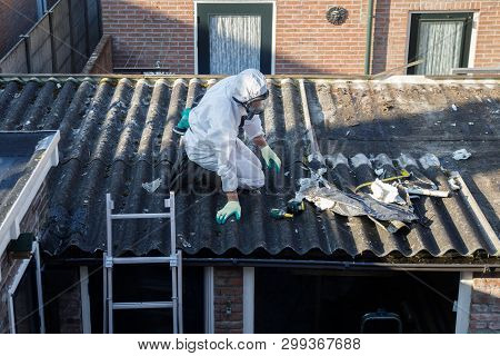 Professional Asbestos Removal. Men In Protective Suits Are Removing Asbestos Cement Corrugated Roofi