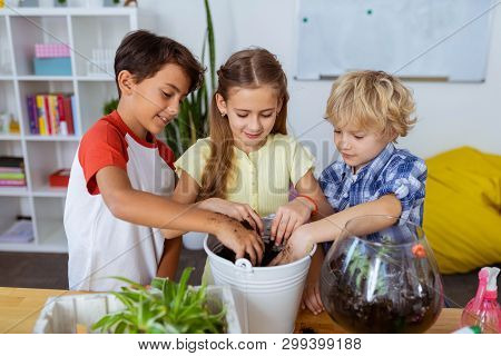 Pupils Feeling Involved In Potting Flowers And Cactuses At School