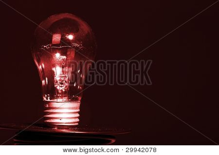 Close Up of light bulb over black background. Electricity.