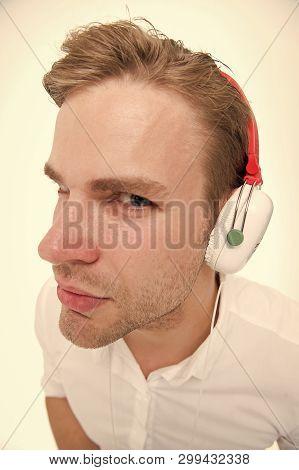 Spy Concept. Man Listening Headphones Suspiciously As Spy. Guy With Earphones Listens Sound. Man Sus