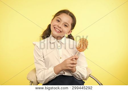 Having fun with candy. Girl cute kid ponytails hairstyle eat sweet lollipop. Sweets in appropriate portions ok. Girl pupil school uniform likes sweet lollipop yellow background. Her favorite flavour. poster