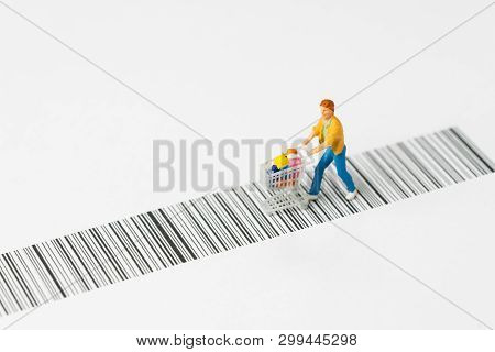 Miniature People Figurine With Grocery In The Shopping Cart Or Trolley Rally On The Bar Code Using A