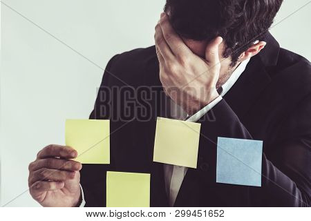 Serious Businessman Feels Disappointed While Looking At Sticky Note On The Windows In The Office. Ba
