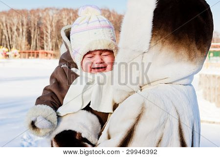 die Mutter mit dem weinenden Baby außerhalb im kalten