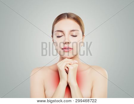 Woman Face. Girl With Clear Skin Relaxing. Woman Puts Hands On The Chest On Grey Background