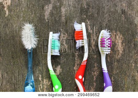 Close Up Of Old Toothbrushes On Wooden Background. Top View. Flat Lay.