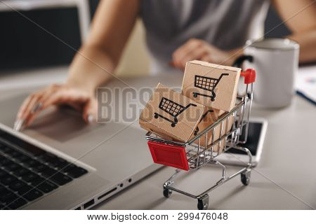 Online Shopping . Ecommerce And Delivery Service Concept : Paper Cartons With A Cart Or Trolley Logo