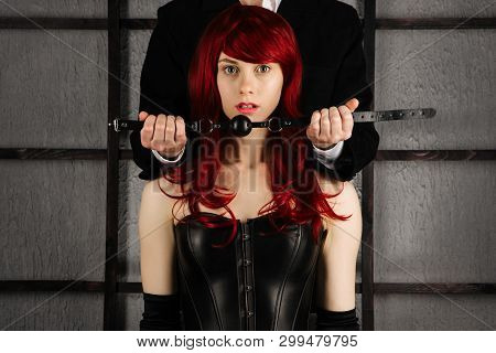 Adult Sex Games. A Man Holds A Gag Near The Mouth Of A Red-haired Girl In A Leather Corset. Bdsm Out