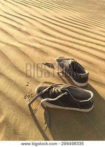 A pair of shoes left in the stark desert sand dunes. Concept for experience the nature closely.