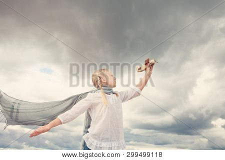 Small Girl With Scarf Playing With Airplane Against The Gray Sky. Freedom Open Concept