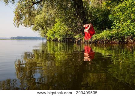 Attractive girl in red dress sits on the river bank. Beauty, fashion, outdoor