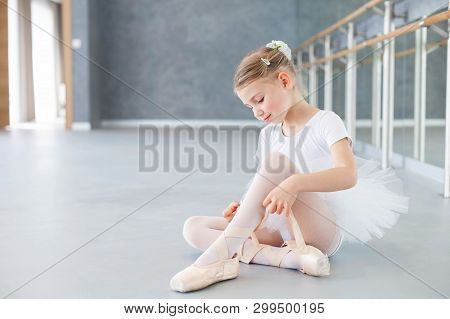 Little Ballerina Is Trying On Pointe Shoes In Ballet Class. Cute Kid Girl Is Sitting On Floor Under