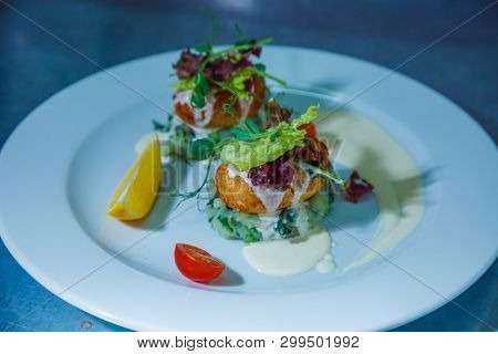 cooked dish of meat on a vegetable cushion on a plate decorated greens