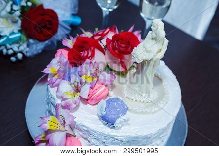 Celebratory cake with figures of the bride and groom decorated flowers and cream on table near the bride's bouquet