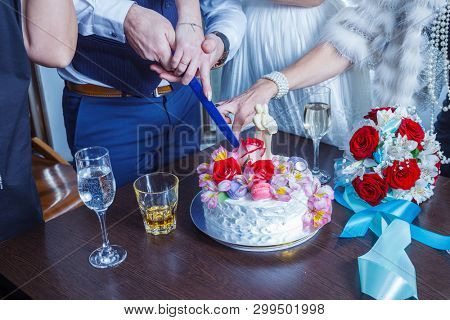 Bride and groom cut the celebratory cake decorated with flowers and cream on the table near the bride's bouquet