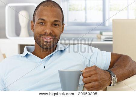 Retrato de alegre hombre de negro guapo sentado en casa con taza en mano, beber té, sonriendo