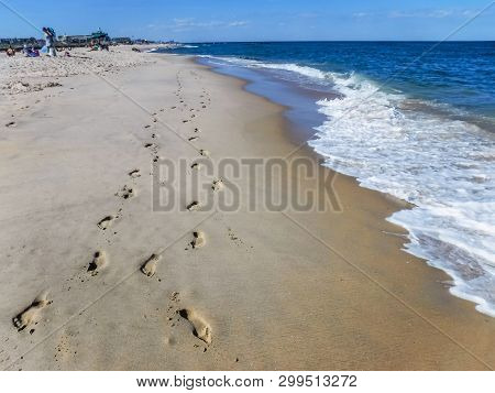 Footprints In The Sand Along The Shoreline In Spring Lake Along The Jersey Shore.