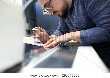 The Printer At The Stage Watches The Print Quality Through A Magnifying Glass.