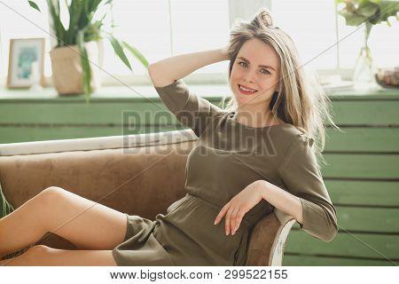 Beautiful girl in a khaki dress in green interior. Charismatic woman having fun in short dress. Nice day poster