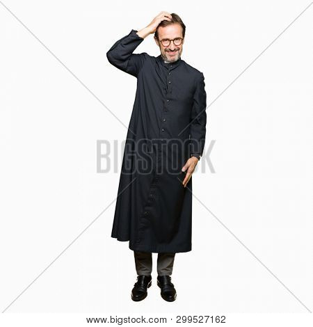 Middle age priest man wearing catholic robe confuse and wonder about question. Uncertain with doubt, thinking with hand on head. Pensive concept.