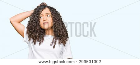 Young beautiful woman with curly hair wearing white t-shirt confuse and wonder about question. Uncertain with doubt, thinking with hand on head. Pensive concept.