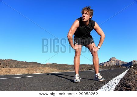 Jogger resting after running. Man runner taking a break during training outdoors in amazing landscape. Young Caucasian male fitness model after work out.