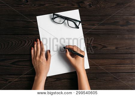 Top View Of Women's Hands, Ready To Write Something On An Empty Piece Of Paper Lying On A Wooden Tab