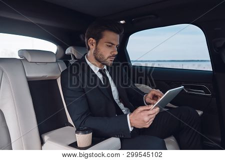 Considering The Next Step. Handsome Young Man In Full Suit Working Using Digital Tablet While Sittin