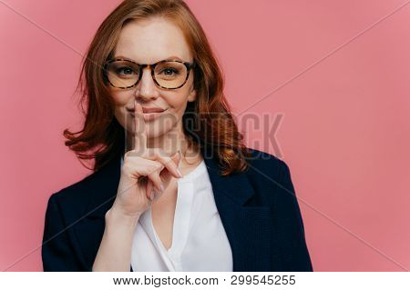 Isolated Shot Of Attractive Secret Woman Keeps Fore Finger Over Lips, Demonstrates Shush Gesture, Te