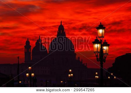 Mysterious Blood Red Sunset Over Salute Basilica (saint Mary Of Health) Domes With Old Street Lamps