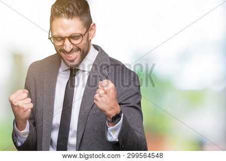 Young handsome business man over isolated background very happy and excited doing winner gesture with arms raised, smiling and screaming for success. Celebration concept.